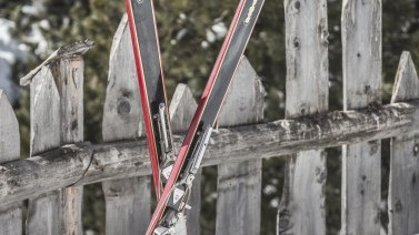 Ski vor traditionellem Holzzaun